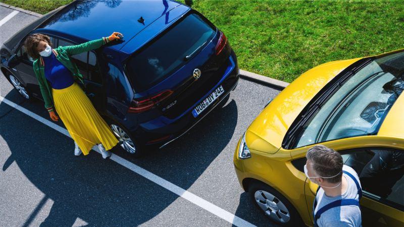 Mujer joven al lado de un Volkswagen Golf azul esperando para entregar las llaves del coche
