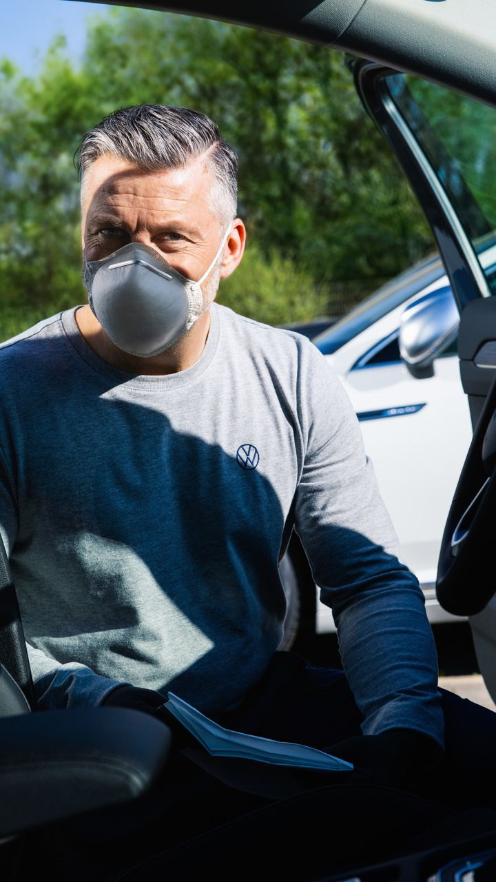 Hombre con mascarilla mirando hacia dentro de un Volkswagen