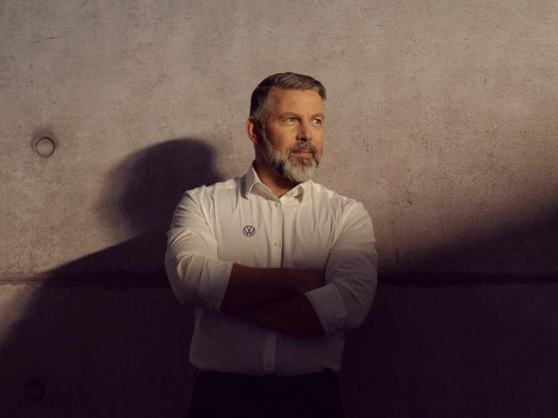 Hombre con camisa blanca y el logo de Volkswagen de brazos cruzados delante de un muro