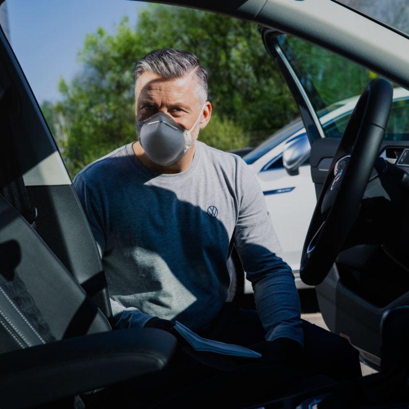 Hombre con mascarilla limpiando en interior de un Volkswagen