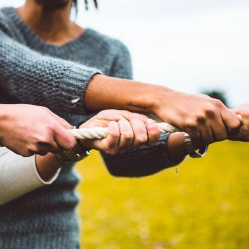 Detalle de manos juntas tirando de una cuerda con un prado detrás