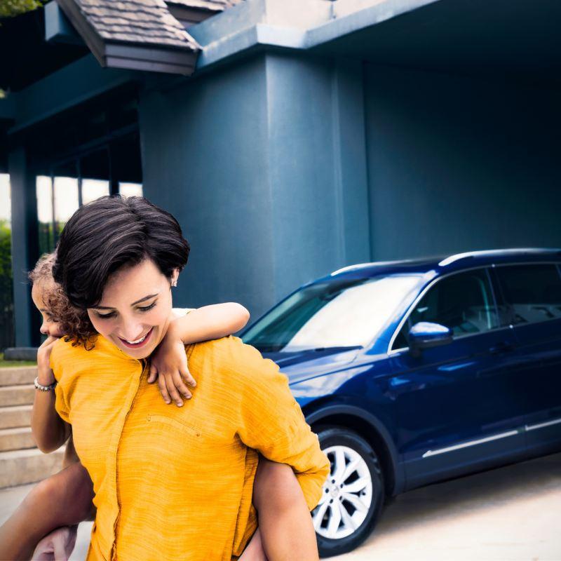 Mujer joven con una niña montada en la espalda delante de un SUV Volkswagen azul