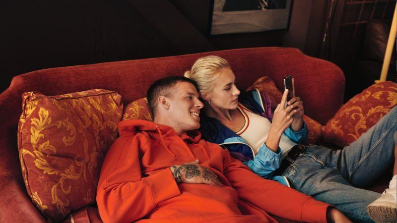 Pareja joven sentada en un sofá mirando un móvil