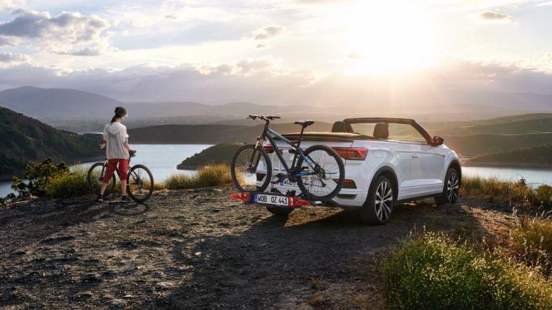 Chica con una bicicleta en la montaña junto a un Volkswagen T-Roc Cabrio blanco con un portabicicletas