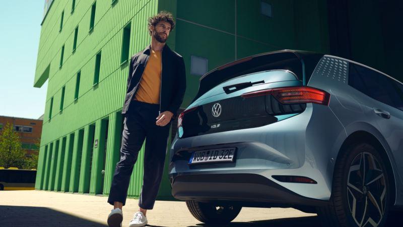 Chico de pie junto a un Volkswagen ID.3 azul visto desde atrás aparcado en la calle