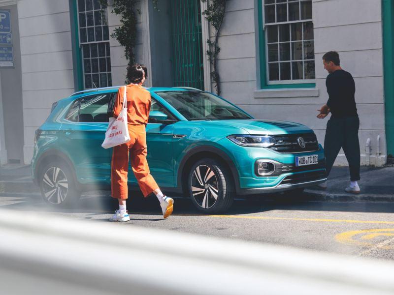 Vista lateral de un T-Cross turquesa aparcado en la calle por el día