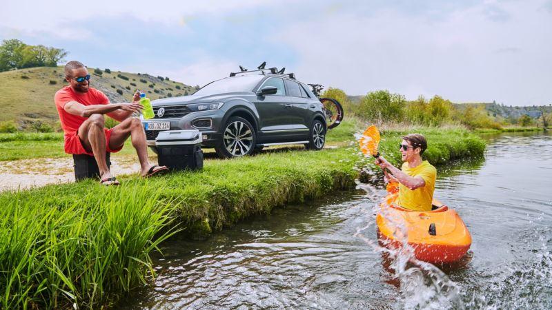 Dos hombres jóvenes en un río con un Volkswagen SUV aparcado en la orilla