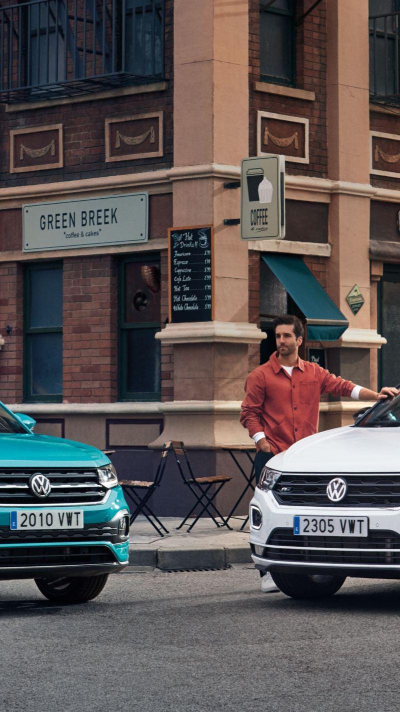 Nuevo T-Cross turquesa y T-Roc bicolor blanco con techo negro aparcados en la acera
