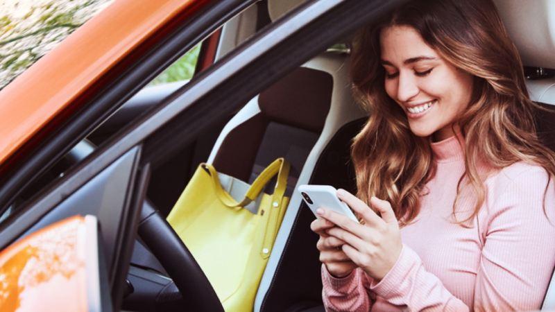 Chica usando un móvil sentada en el interior de un Volkswagen