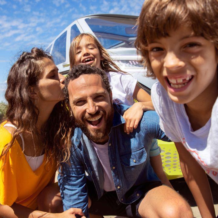 Familia sonriendo al aire libre delante de un Volkswagen