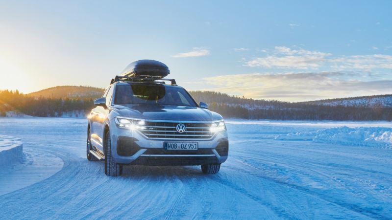 Volkswagen Touareg con baúl de techo en la nieve