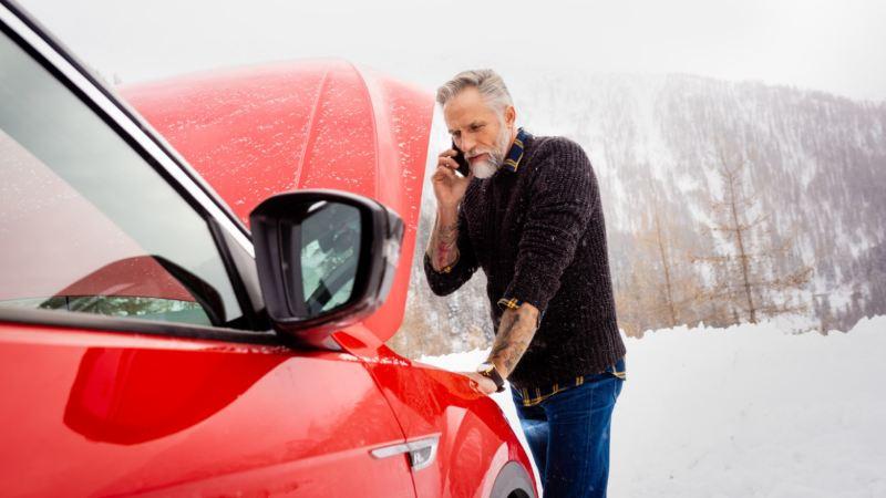 Hombre llamando por teléfono mirando el capó abierto de un Volkswagen rojo bajo una nevada
