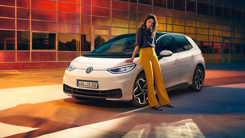 Chica joven apoyada en un Volkswagen ID.3 blanco