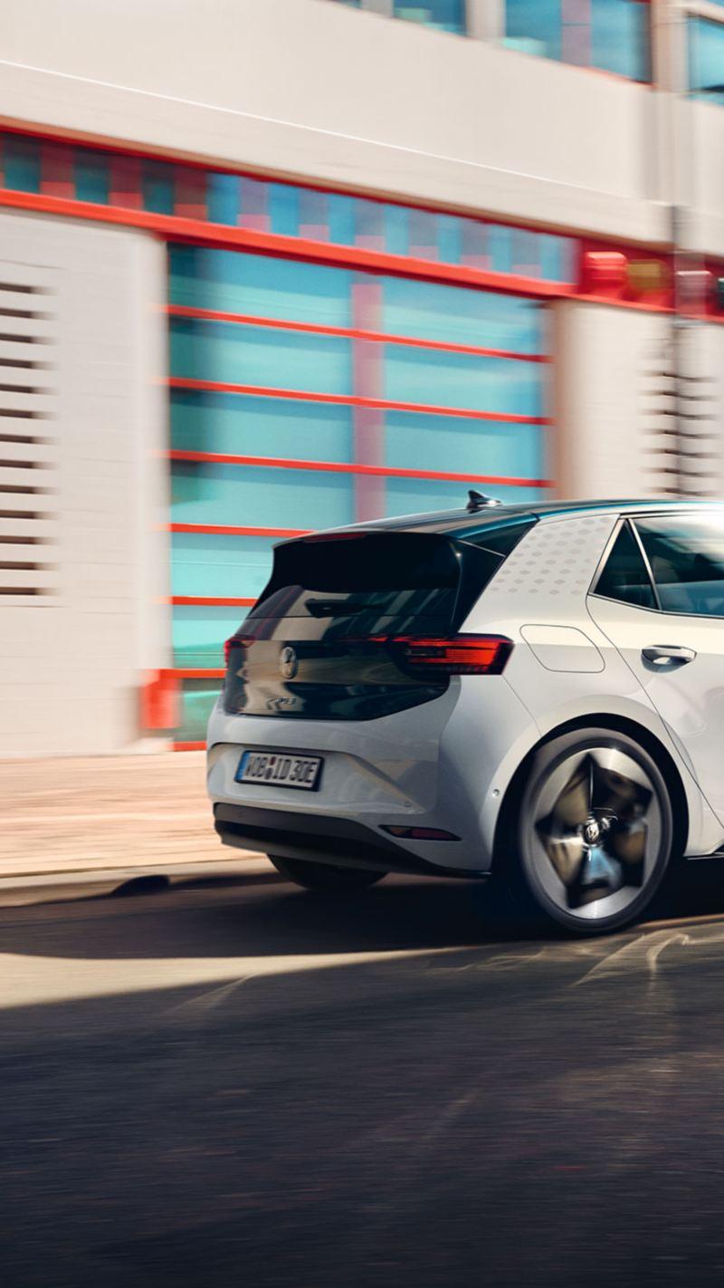 Vista laterial de un Volkswagen ID.3 blanco circulando por la ciudad
