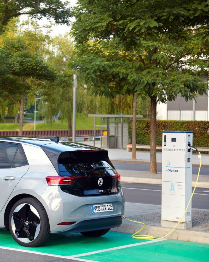 Volkswagen ID.3 plateado aparcado en la calle enchufado a una estación de carga