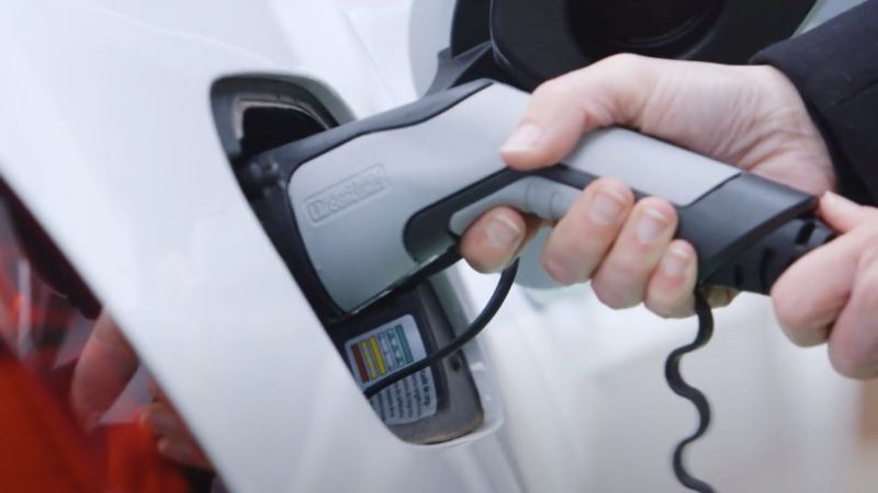 Detalle de una mano sujetando un enchufe eléctrico conectado a un Volkswagen
