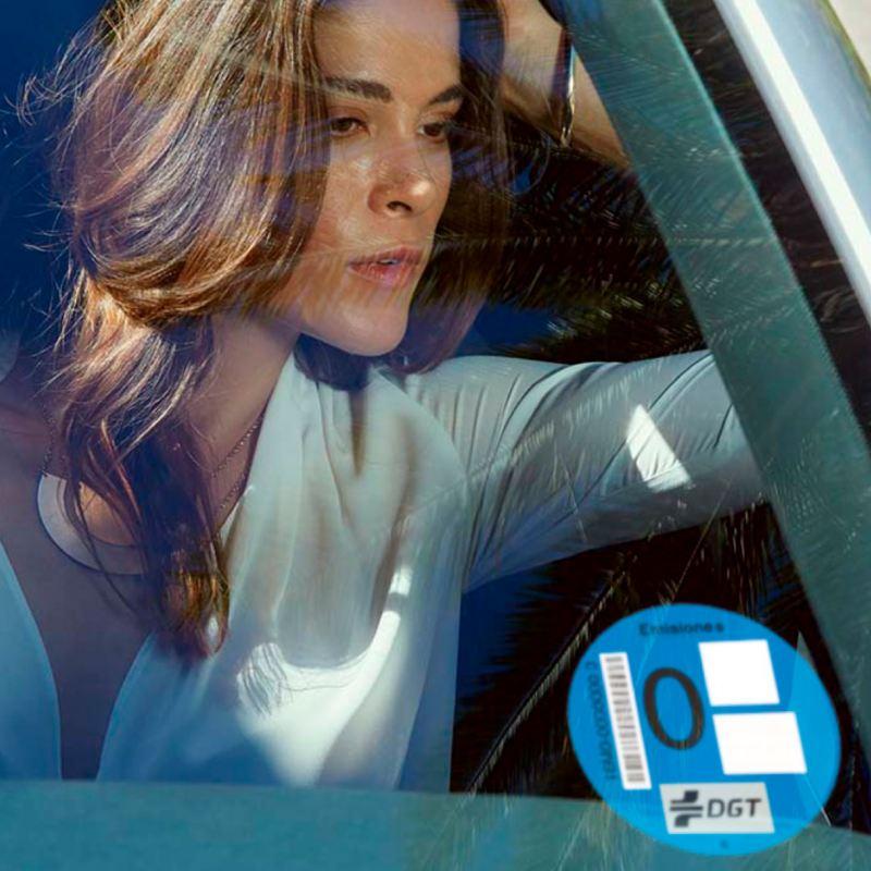 Chica joven vista a través de de la luna de un vehículo Volkswagen con etiqueta 0