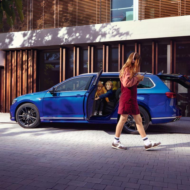 Chica con unos cascos andando frente a un Passat Variant azul con las puertas abiertas y dos niños