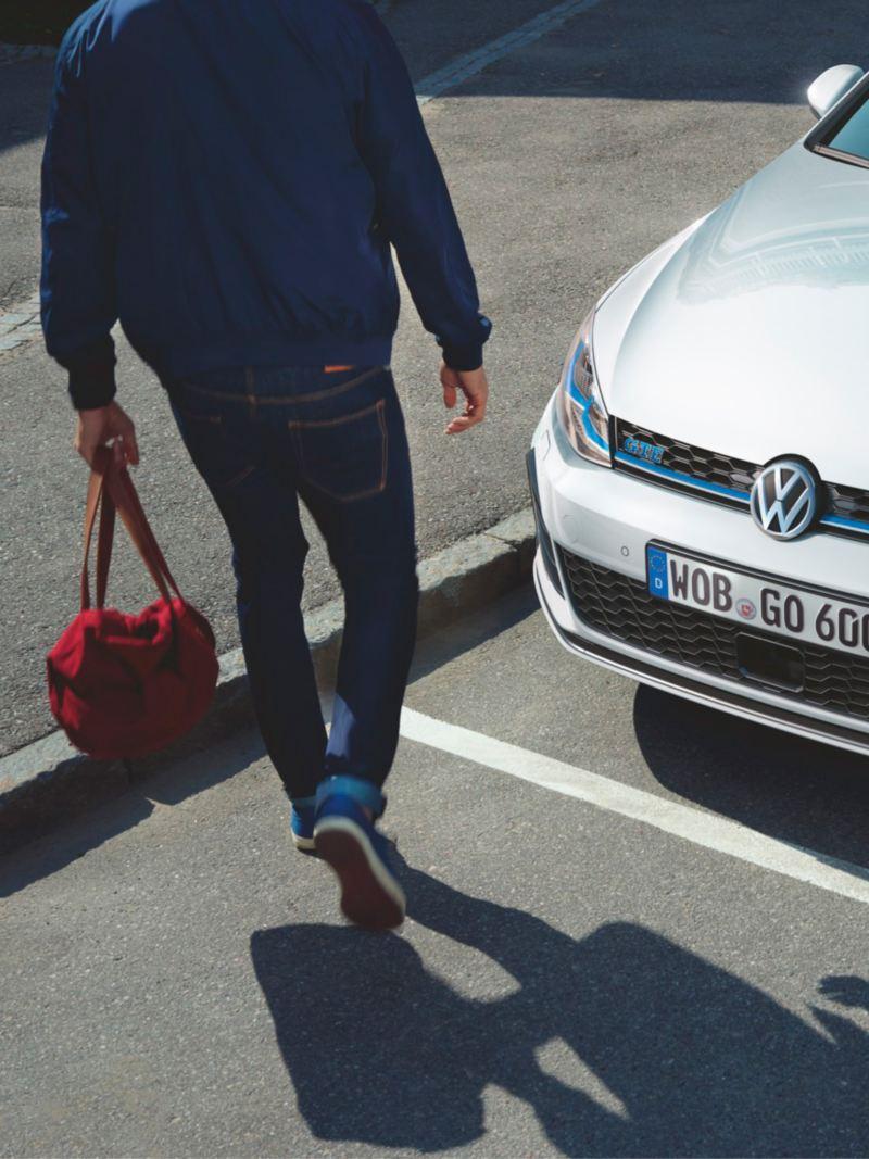 Chico un una bolsa roja en la mano pasando frente a un Golf GTE blanco aparcado en la calle