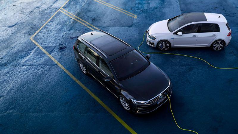 Volkswagen Passat Variant GTE y Golf GTE conectados a la carga eléctrica vistos desde arriba sobre asfalto