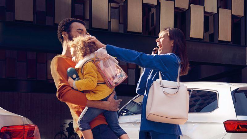 Pareja joven con una hija en brazos saliendo de un Passat GTE blanco