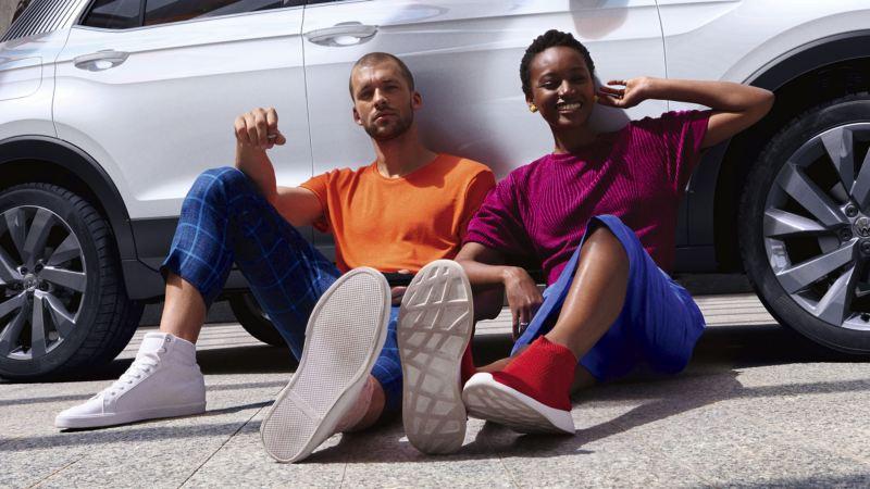 Pareja joven sentados en el suelo apoyados en un T-Cross First Edition blanco