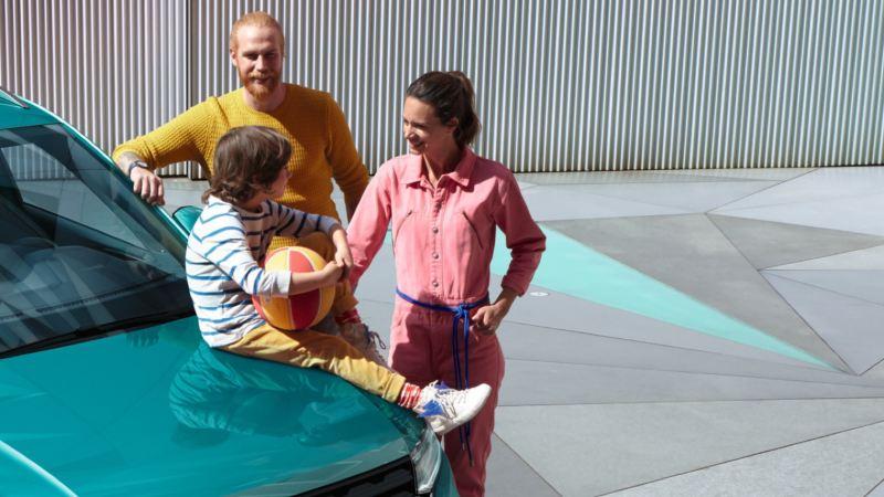 Familia joven con un niño sentado sobre el capó de un T-Cross azul turquesa