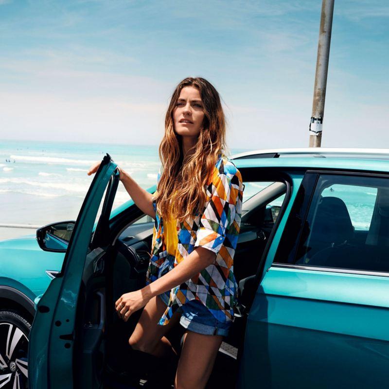 Chica joven saliendo de un T-Cross turquesa en la playa