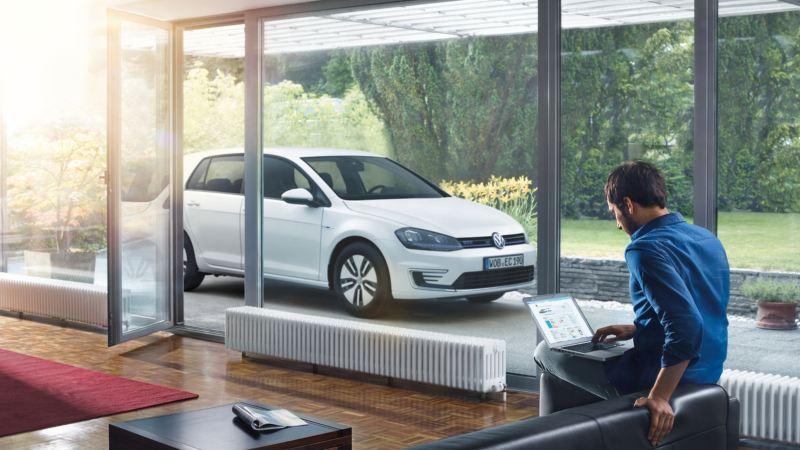 Chico en su casa utilizando un ordenador portátil junto a un Golf GTE aparcado en el porche