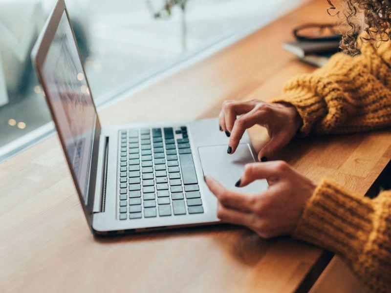 Manos de mujer utilizando un ordenador portátil en la mesa de un bar
