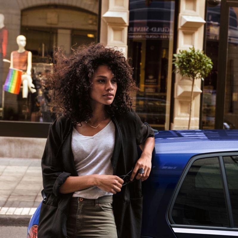 Chica joven apoyada en un Volkswagen Golf azul aparcado en la calle