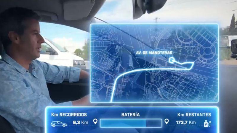Hombre joven conduciendo un coche eléctrico con gráficas de ruta y autonomía sobre impresas