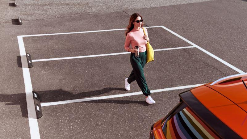 Mujer joven caminando en un parking hacia un Volkswagen que se ve parcialmente