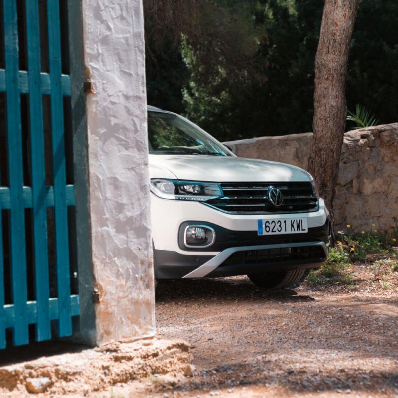 Frontal de un Volkswagen Tiguan asomándose detrás de una reja en un camino de tierra