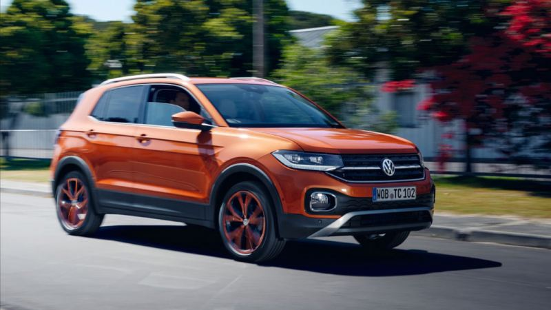 Volkswagen T-Cross color naranja circulando por la ciudad