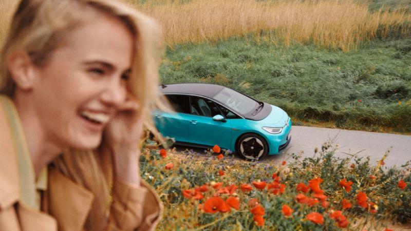 Volkswagen ID.3 azul aparcado en el campo con una chica en primer plano sonriendo