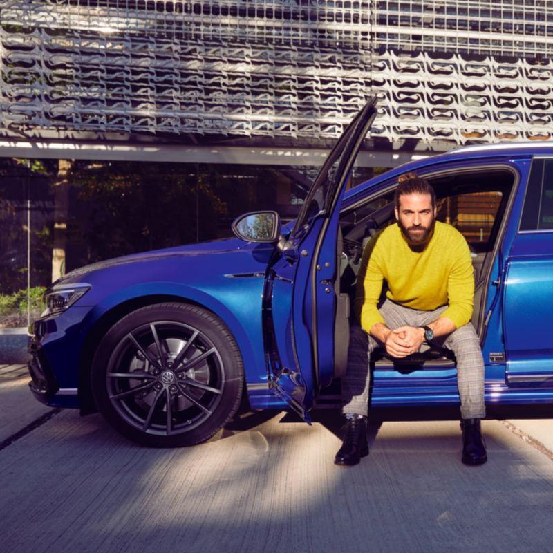 Hombre sentado en el asiento de un Passat Variant azul con las piernas fuera del coche