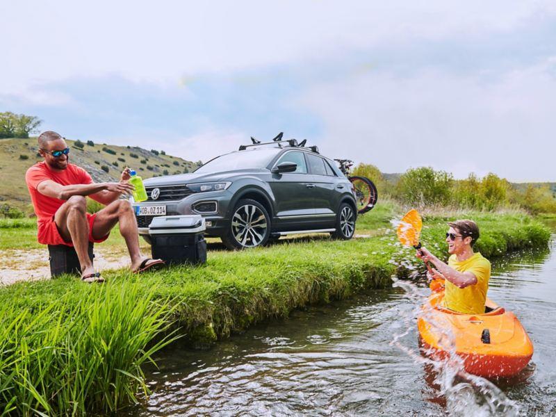 Un joven sonriendo sentado en la orilla de un río junto a otro en un kayak delante de un Volkswagen SUV aparcado en la orilla