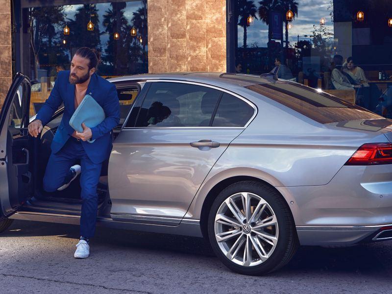 Hombre joven de traje azul bajando de un Passat gris aparcado en la ciudad
