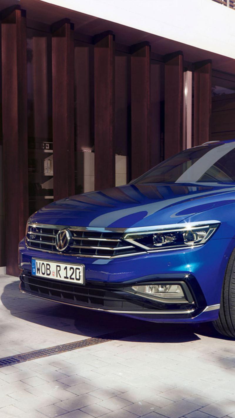 Padre con hijos con un Volkswagen Passat Variant azul visto de frente aparcado en casa