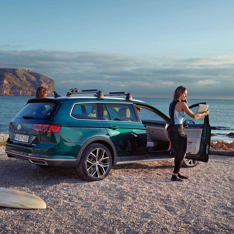 Dos mujeres jóvenes con un Volkswagen Passat Alltrack aparcando en una playa frente al mar