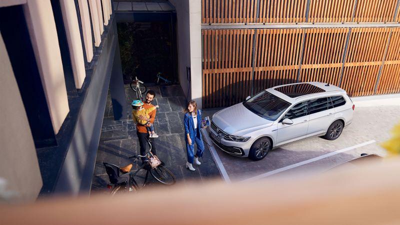 Familia delante de un Passat GTE conectado a la red eléctrica aparcado en casa