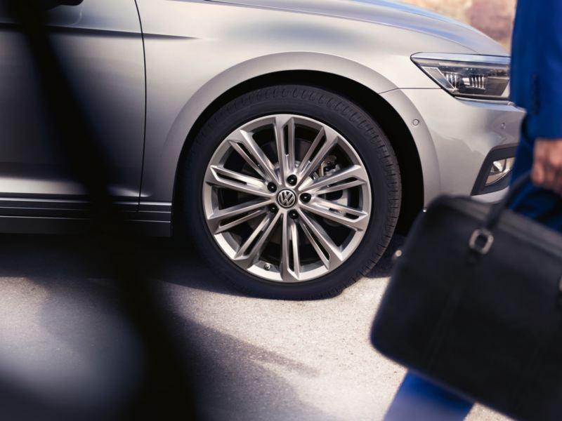 Hombre con maletín delate de un Volkswagen Passat Variant gris