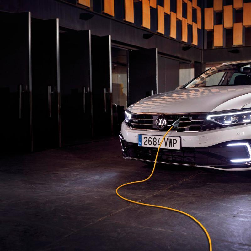Passat Variant GTE blanco en un garage visto de frente y realizando una carga eléctrica
