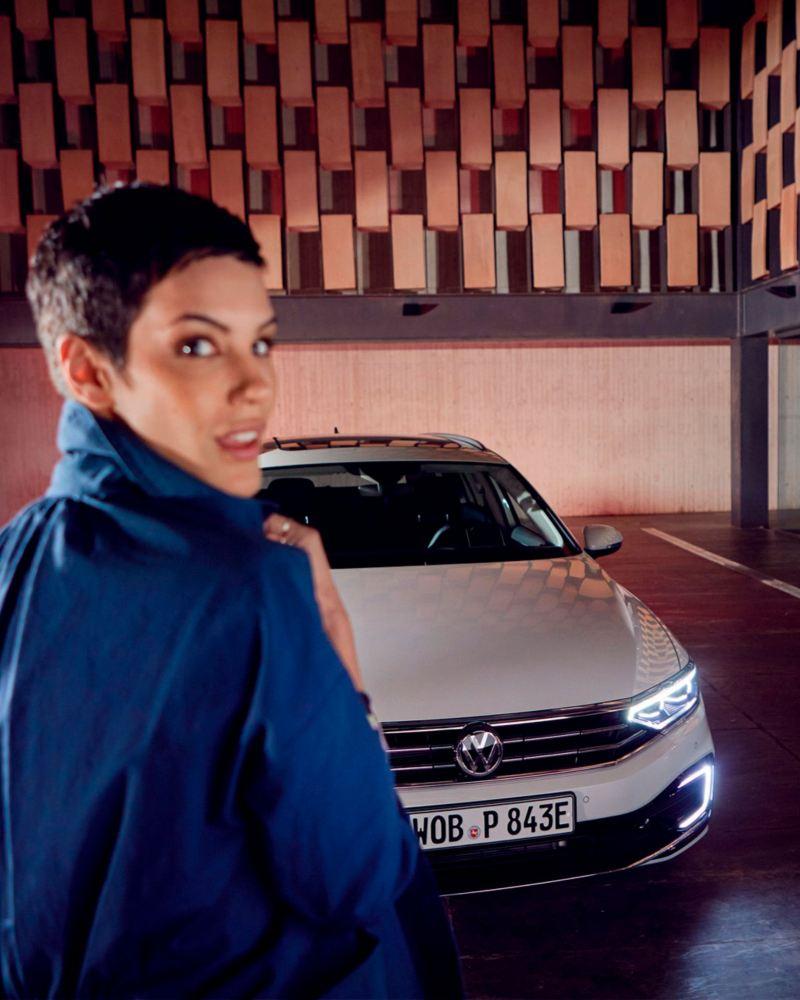 Mujer de pie delante de un Volkswagen Passat Variant GTE