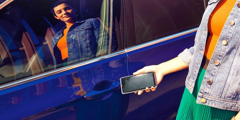 Mujer acercando un móvil a la cerradura de un Volkswagen Passat Variant GTE