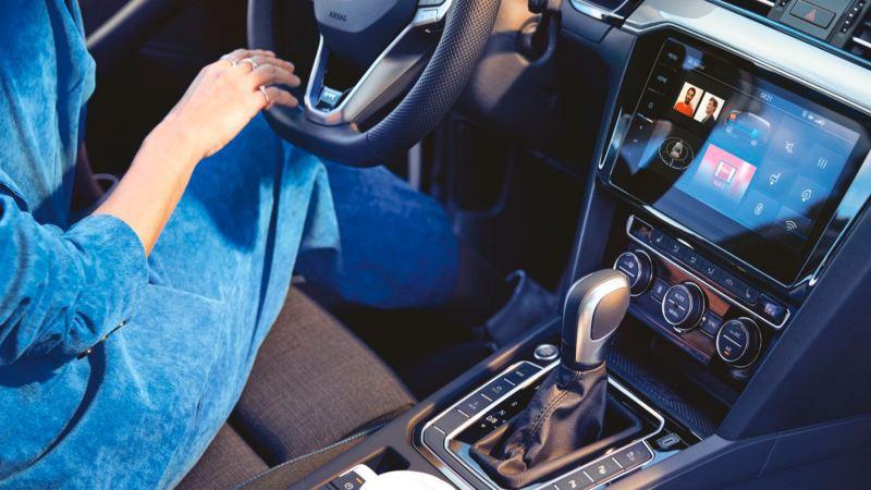 Mujer al volante de un Volkswagen Passat Variant GTE, vista de la pantalla interactiva