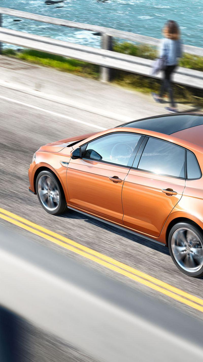 Volkswagen Polo naranja visto desde arriba circulando por una carretera junto al mar