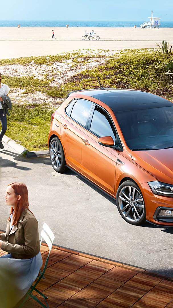 Gente al rededor de un Volkswagen Polo naranja aparcado y visto desde arriba