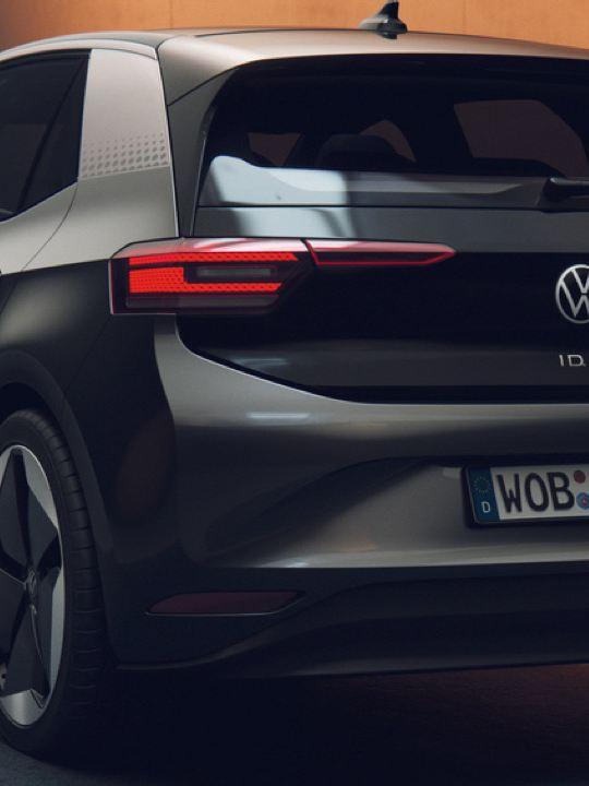 Vista en tres cuartos de un Volkswagen ID.3 gris aparcado en un hangar en penumbra